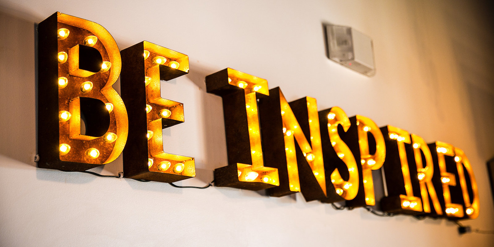 Vintage marquee sign that says be inspired.
