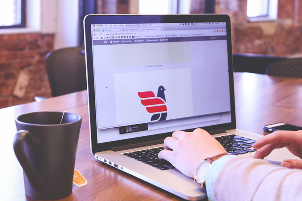 close up of a person working on a logo design on a laptop