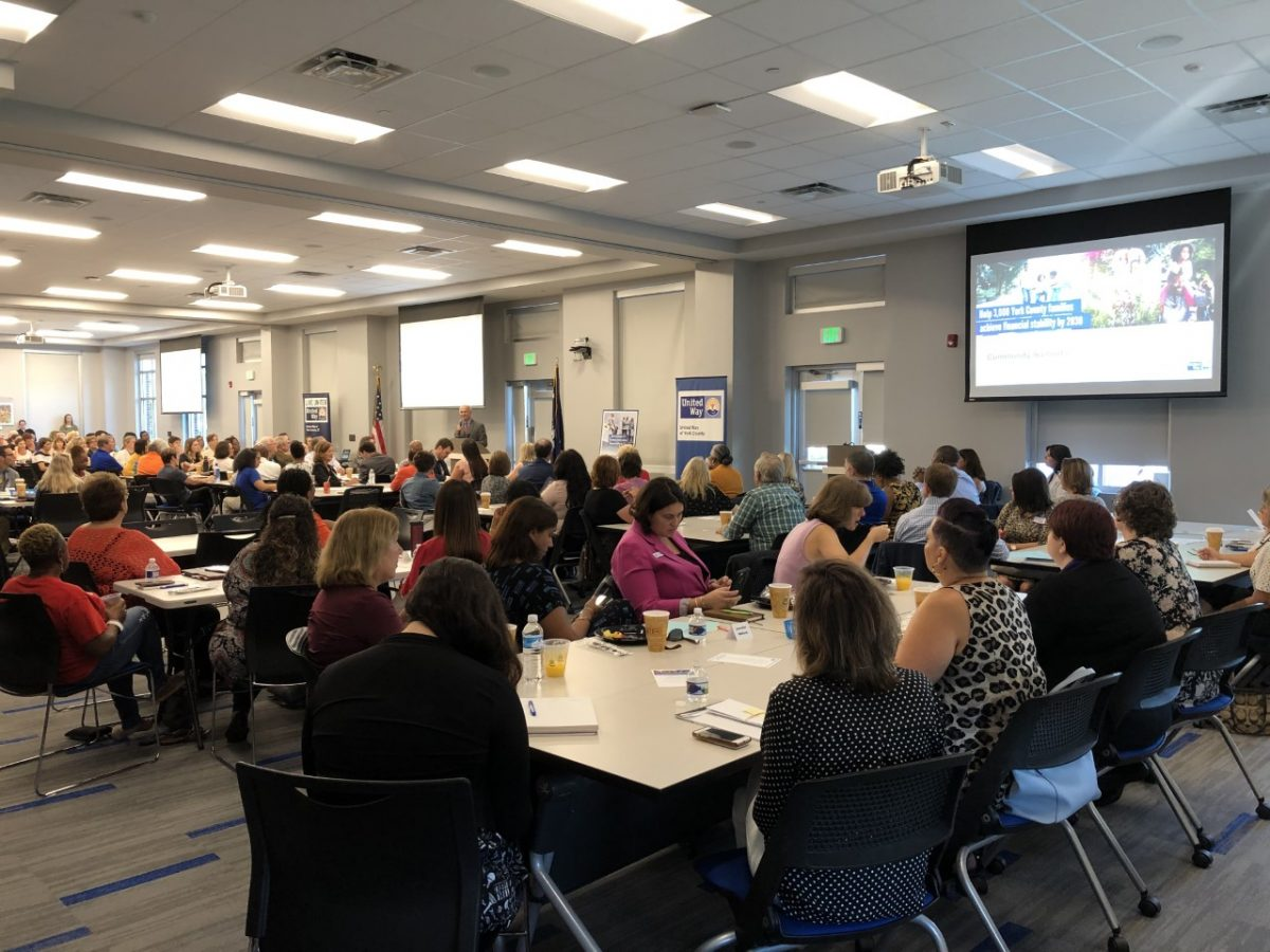 Members of the United Way present to a large conference room of people