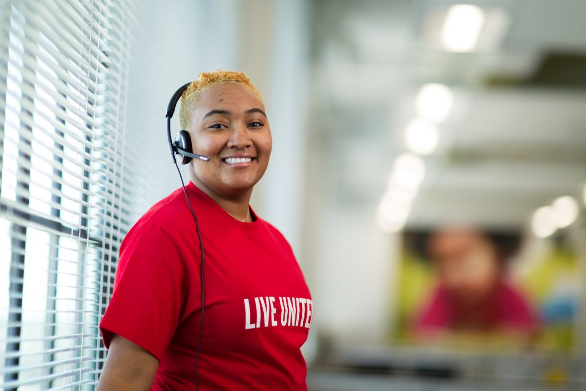 A United Way 211 operator smiles while wearing a phone headset