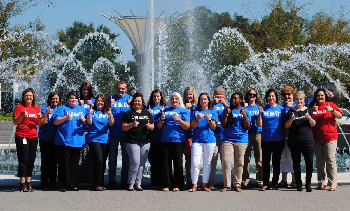A group of volunteers smile together in a group shot in front of the big fountain in downtown Rock Hill, SC